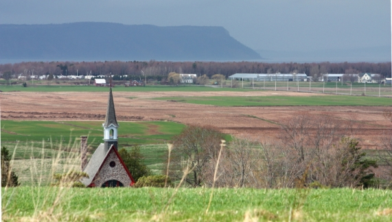 View north from the hay field overlooking the memorial church at Grand-Pré National Historic Site. Are there archaeological remains underfoot?